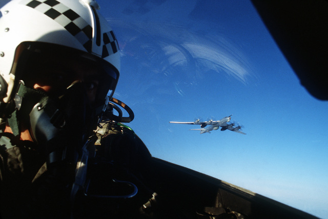 A view of the pilot of an F-4 Phantom II aircraft, taken from inside the cockpit, observing a Soviet Tu-95 Bear aircraft flying over international waters