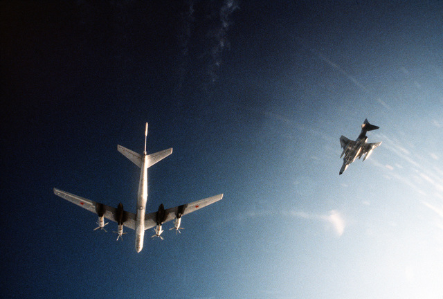 AN air-to-air underside view of a Soviet Tu-95 Bear aircraft, left, being observed by a U.S. Air Force F-4 Phantom II aircraft over international waters
