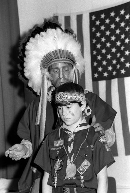 SSGT Kenneth Paulini, in Indian attire, inducts his son, Scout Kevin Paulini, into Webelow at a Statement of Word ceremony in the Skyraider Recreation Center at Tempelhof Central Airport