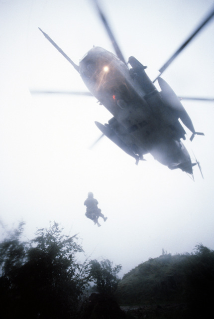 "A1C Scott Gearen and Dutch ""survivor"" MSGT Albert Van Rhijin are lifted aboard a CH-53 Sea Stallion helicopter during exercise REFORGER '80"