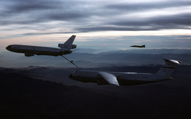 AN air-to-air left side view of a C-5 Galaxy aircraft approaching a KC-10 Extender aircraft for refueling