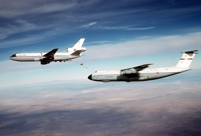 AN air-to-air left side view of KC-10 Extender aircraft moving away from a C-5 Galaxy aircraft after refueling it