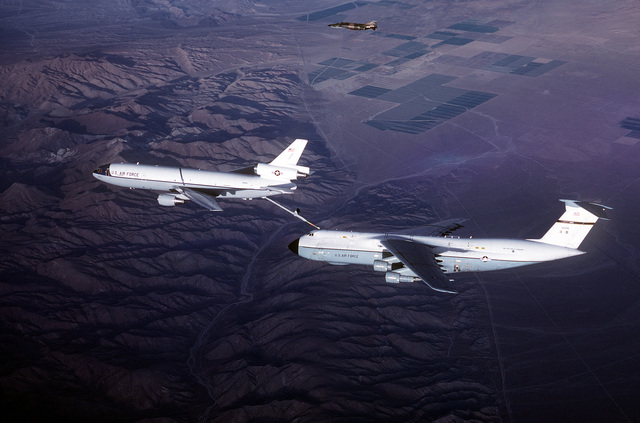 AN air-to-air left side view of KC-10 Extender aircraft refueling a C-5 Galaxy aircraft. AN F-4 Phantom II aircraft can be seen in the background