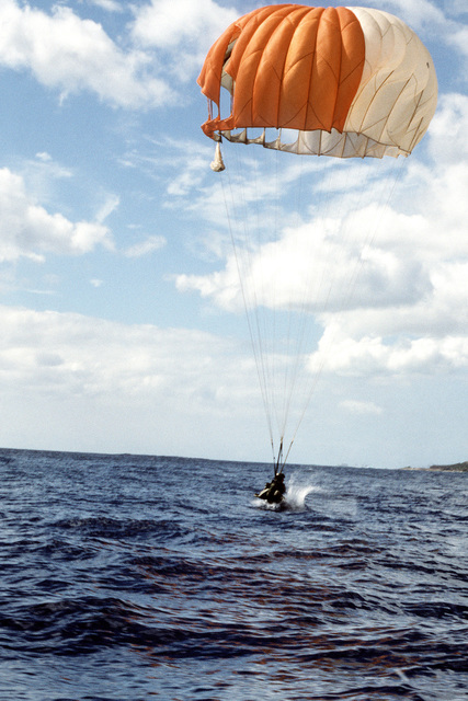 A combat control team member parachutes into the water of Pokai Bay