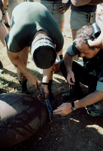 Members of the combat control team (CCT) attach an explosive device to a training bomb