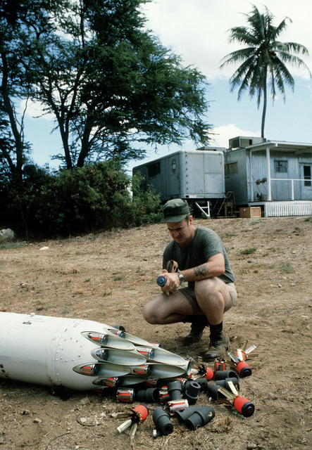 MSGT Adams, of the combat control team (CCT), takes a closer look at one of the many types of bomblets used in the canister