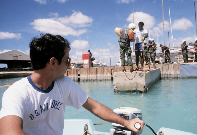SGT Scruggs of the 15th Air Base Wing support organization operates a boat that drags members of a combat control team through the water during parachute training