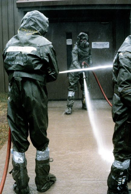 Dressed in chemical warfare gear, Disaster Preparedness personnel decontaminate one of the base facilities during a chemical warfare exercise
