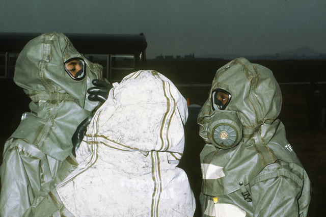 A decontamination team wearing chemical warfare gear takes part in a chemical warfare exercise. The team is from the 8th Tactical Fighter Wing