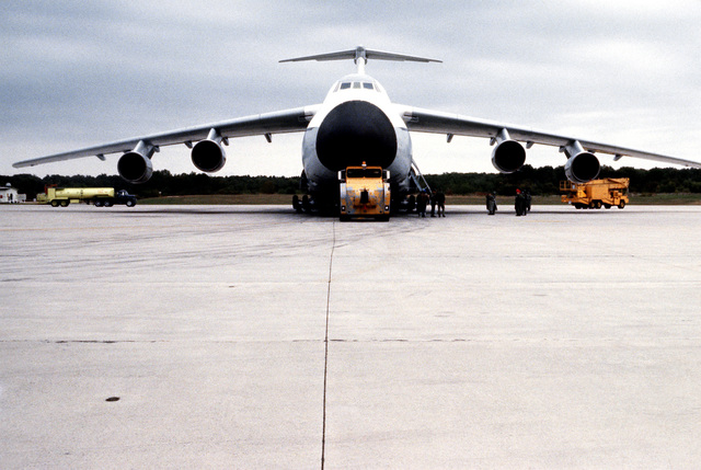 A C-5A Galaxy aircraft is towed into position for the decontamination phase and the end of the test project during a chemical warfare defense equipment test
