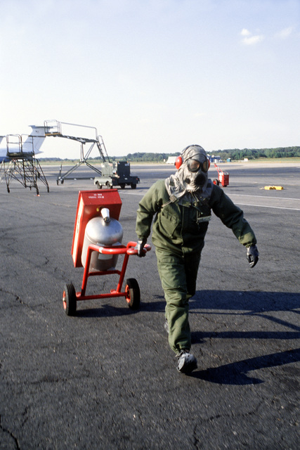 A member of the 436th Military Airlift Wing, dressed in chemical warfare gear, pulls a fire extinguisher into position during a chemical warfare defense equipment test