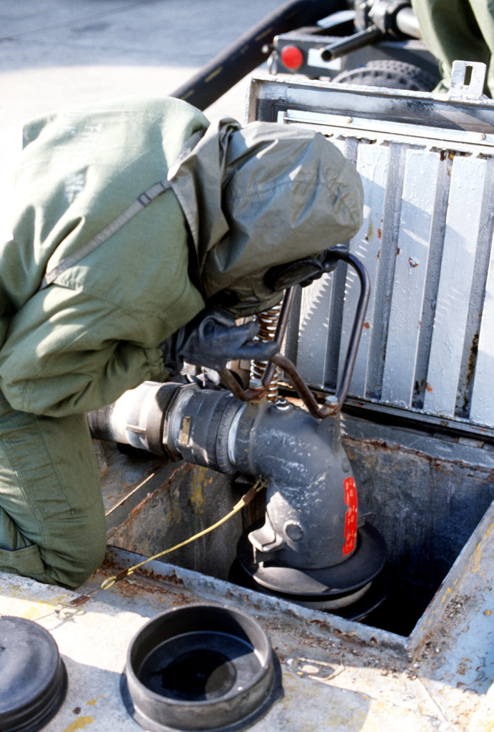 A member of the 436th Military Airlift Wing, wearing chemical warfare gear, defuels an aircraft during a chemical warfare defense equipment test
