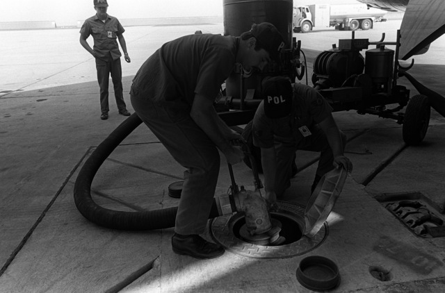 A1C Bill Adams and SSGT Randall Simeona hook up an MH-2A hose cart to refuel a B-52 Stratofortress aircraft. The airmen are from the Fuels Management Branch, 22nd Supply Squadron, 22nd Bombardment Wing. The branch was recently named one of the top three units in the Strategic Air Command