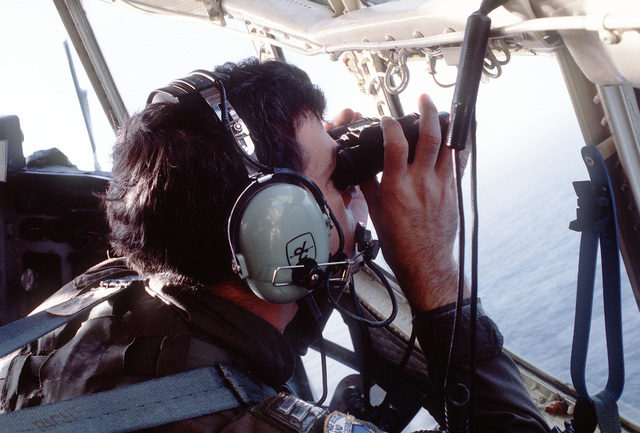 A member of the 33rd Aerospace Rescue and Recovery Squadron searches with binoculars for targets dropped from the cockpit of an HC-130 Hercules aircraft at the start of Operation Cope Angel