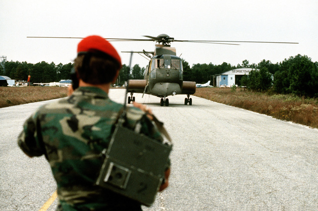 A member of the 437th Combat Controllers, Charleston Air Force Base, guides an HH-53 Super Jolly helicopter onto the runway at Georgetown Municipal Airport during exercise Thunderhog II '80
