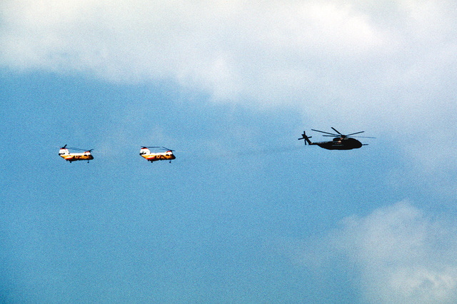 A right side view of an HH-53 Super Jolly helicopter and two H-46 helicopters in flight during Operation Cope Angel