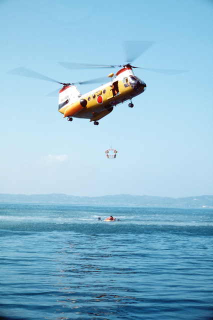 """AN H-46 helicopter from the Japanese Air Self Defense Force picks up a """"survivor"""" from the water during Operation Cope Angel"""