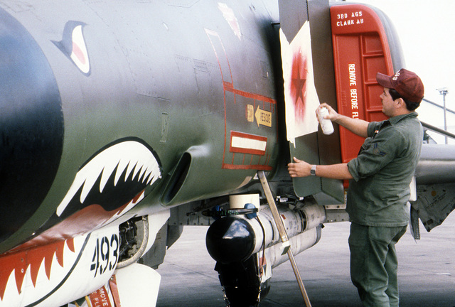 A 3rd Tactical Fighter Wing member spray paints a design on an F-4E Phantom II aircraft during exercise Cope North '80. AN ALQ-119 electronic countermeasure pod is mounted on the fuselage of the aircraft