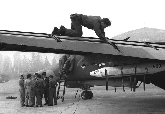 A crew chief inspects the wing struts of an F-111F aircraft as Italian air force pilots view the flight controls of the aircraft. The airman is assigned to the 48th Field Maintenance Squadron