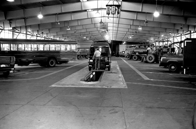 An airman of the 52nd Transportation Squadron prepares to work on a van positioned over a grease pit at the maintenance shop