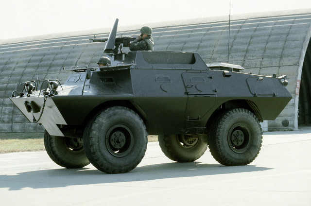 A security policeman patrols the area in an armored personnel carrier (APC)