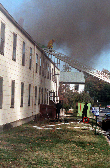 A fire-engine tower ladder and hoses are being set up for fighting a fire, which is burning the CHIEF of Chaplains Building