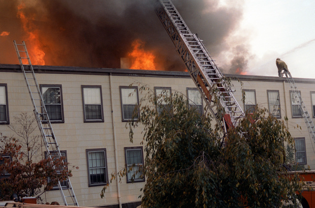 A fire-engine tower ladder is set up for fighting a fire, which is burning the CHIEF of Chaplains Building