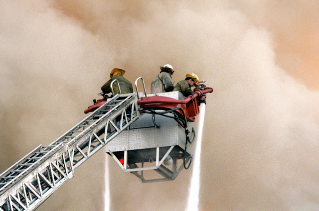 Firemen, on a fire-engine tower ladder, fight a fire, which is burning the CHIEF of Chaplains Building