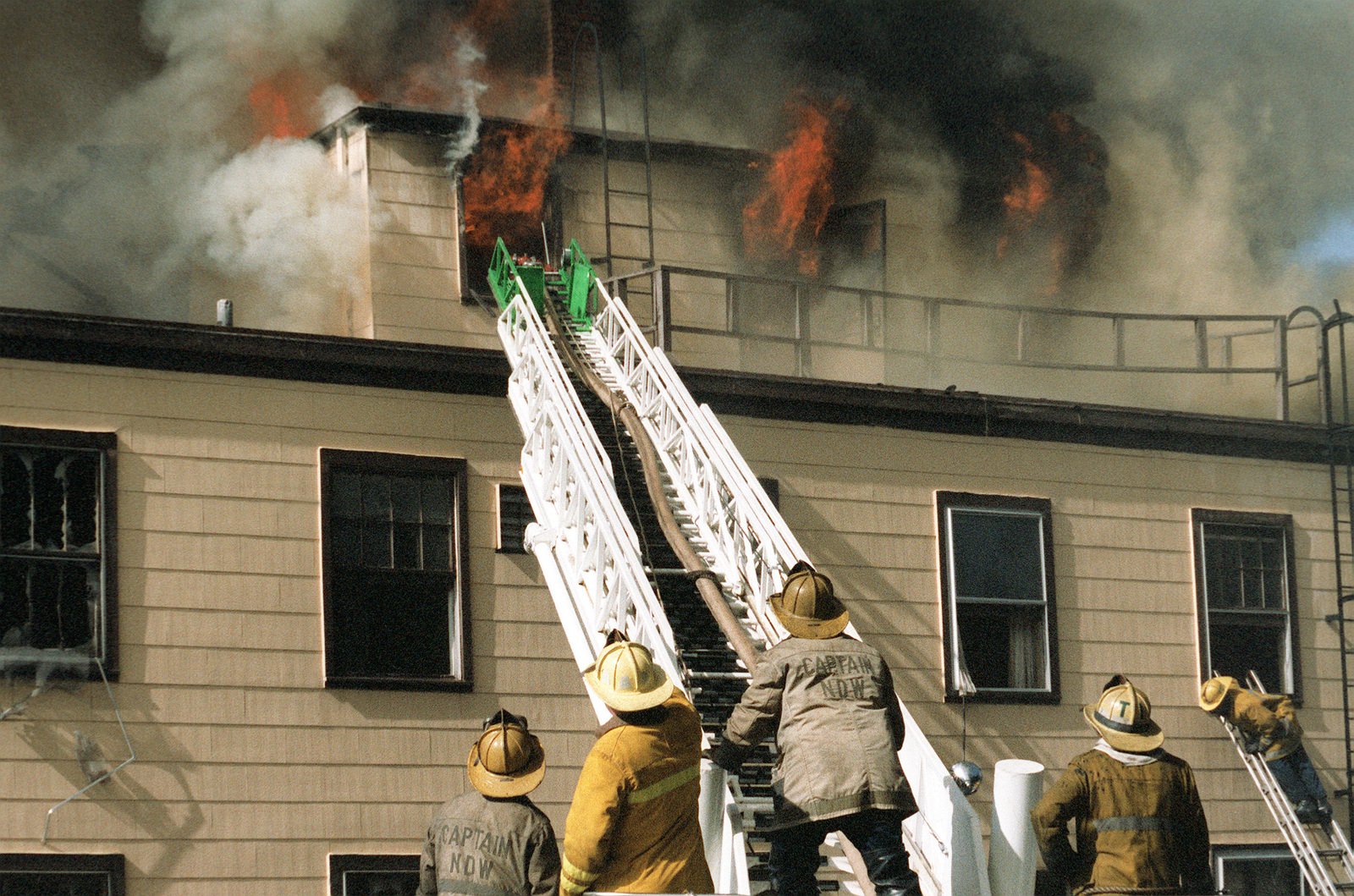 Firemen raise a fire-engine tower ladder toward one of the windows of the blazing CHIEF of Chaplains Building