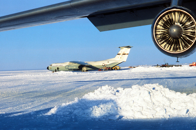Left side view of a C-141 Starlifter aircraft with another aircraft's wing in the foreground during Operation Deep Freeze '80