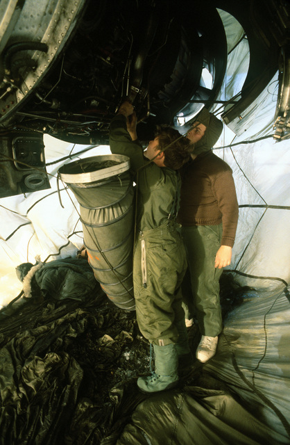 Members of the 619th Military Airlift Support Squadron (MASS), prepare to use a heating system for working on a C-141 aircraft engine during Operation Deep Freeze '80. The shelter constructed to protect them from minus 60-degree weather