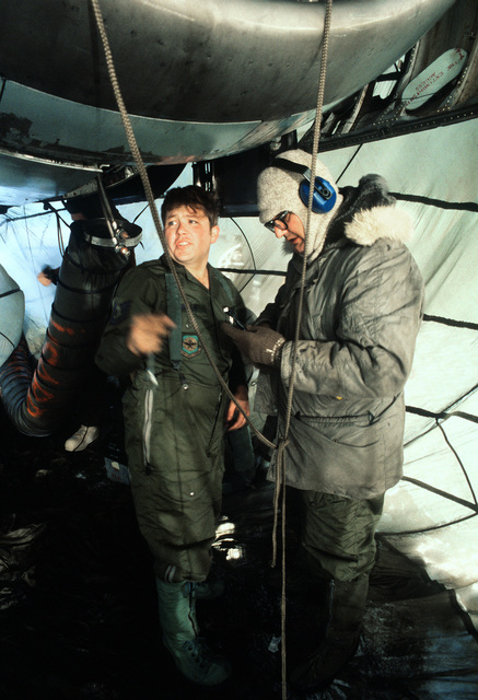 Members of the 619th Military Airlift Support Squadron (MASS) work on the engine of a C-141 Starlifter aircraft during Operation Deep Freeze '80. The airmen are inside a makeshift constructed to protect them from minus 60-degree weather