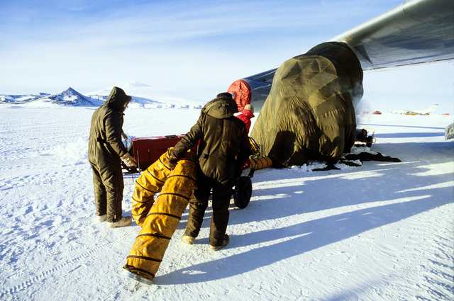 Members of the 619th Military Airlift Support Squadron (MASS), working on a C-141 Starlifter aircraft engine, hook up a heating unit to a makeshift shelter during Operation Deep Freeze '80