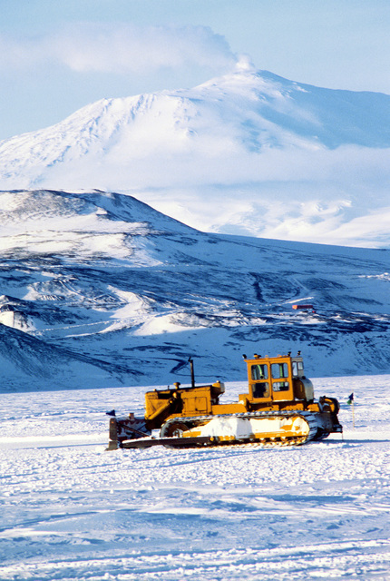 Side view of a snow plow with Mount Eribus in the background during Operation Deep Freeze '80