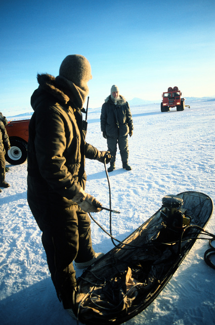U.S. Navy ground support personnel ready a sled-mounted air pump during Operation Deep Freeze '80