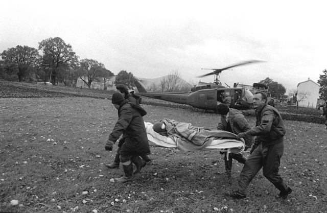 A native patient is carried to a waiting helicopter (not visible) as an Army UH-1H Iroquois helicopter (background) prepares for take-off. The patient was injured during a major earthquake on November 23