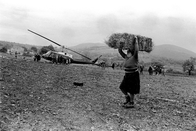 A native woman carries a bale of hay on her head as other natives gather around a UH-1H Iroquois helicopter. The helicopter has airlifted relief supplies following a major earthquake on November 23