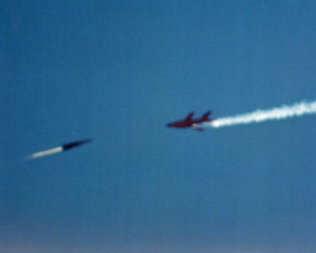 A Standard-ER/SM-2 (RIM-67) surface-to-air missile, right, just launched from the Vertical Launching System (VLS), approaches a BQM-34A target drone during VLS testing