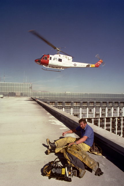 A UH-1N Iroquois helicopter approaches a roof where an exhausted firefighter rests. Firefighters are battling a fire in the MGM Grand Hotel