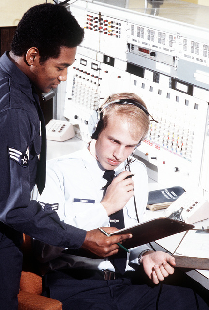 A1C Robert Thomas, radio operator, and SGT Theodore Walker, shift supervisor, search for a particular log entry in the phone patch log book of the Communications Relay Center, Aeronautical Station, 1974th Communications Group, Air Force Communications Command (AFCC)