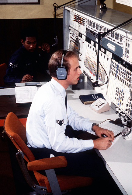 A1C Robert Thomas, radio operator, runs phone patches in the Communications Relay Center, Aeronautical Station, 1974th Communications Group, Air Force Communications Command (AFCC). In the background, SGT Theodore Walker, shift supervisor, logs phone patch entries