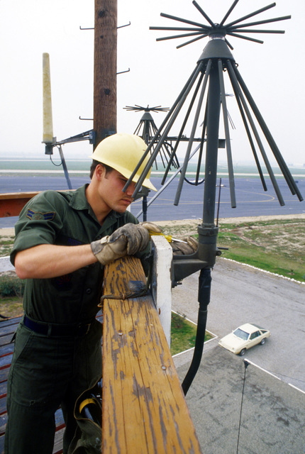 AIC Jim W. Hunt, a ground radio technician assigned to the 1965th Communications Squadron, Air Force Communications Command (AFCC), tightens down one of the antennas on a receiver site