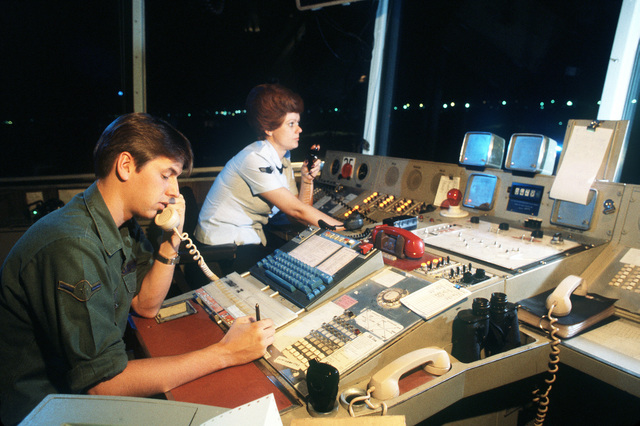 AIRMAN Gary Zeis and AIRMAN 1ST Class Retta Hart, air traffic controller from the 2048th Communications Squadron, maintain radio contact with the ground control approach trailer and an aircraft, from their station in the control tower