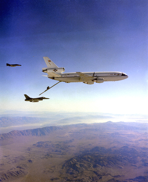 AN air-to-air right side view of a KC-10A Extender aircraft getting into position to refuel an F-16A Fighting Falcon aircraft as an F-4 Phantom II aircraft acts as a chase plane