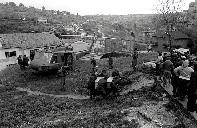 An Army tent (boxed up) is carried up a hill away from a UH-1H Iroquois helicopter during relief efforts after a major earthquake on November 23