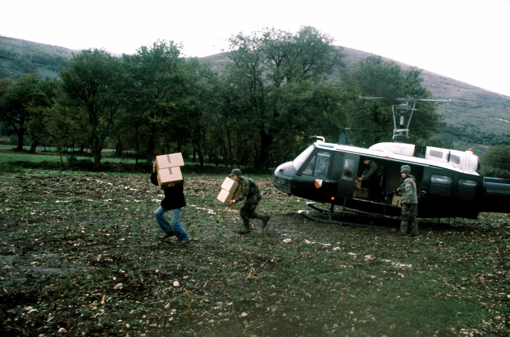 Army paratroopers from 1ST Battalion, 509th Infantry, Vicenza, unload boxes of clothing from a UH-1H Iroquois helicopter during relief efforts after a major earthquake on November 23