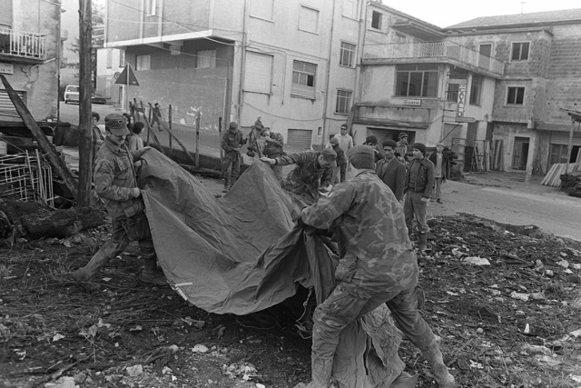 Army personnel from 1ST Battalion, 509th Infantry Regiment, Vicenza, help local citizens set up a tent. The Army is helping after a major earthquake on November 23