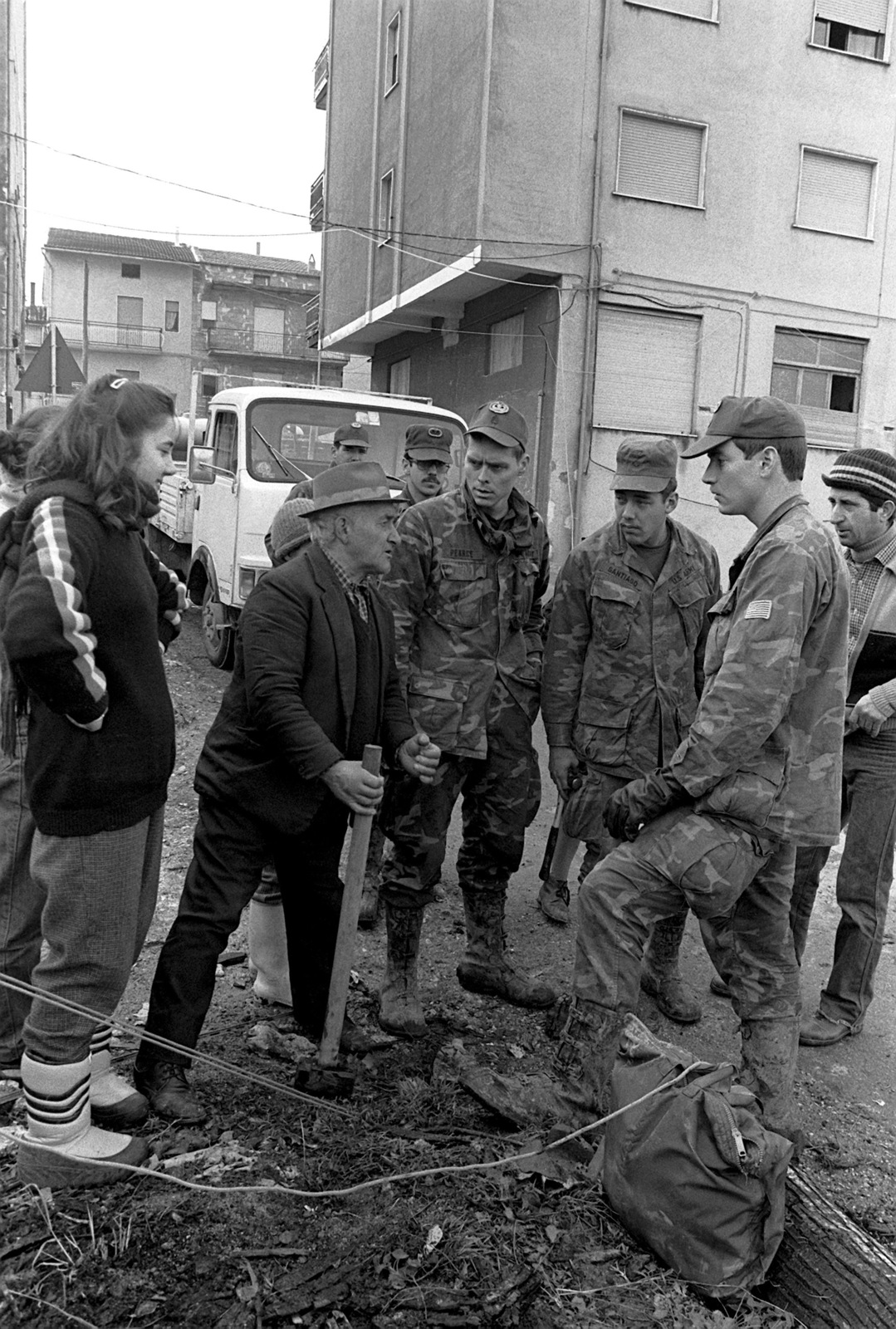 Army personnel from 1ST Battalion, 509th Infantry Regiment, Vicenza, listen as a local citizen asks for tent stakes. The men are helping after a major earthquake on November 23