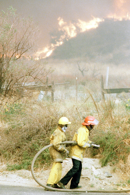 Firefighters battle fires in farmland during the four-day Panorama brush fire, which started in canyons north of town and has been whipped out of control by 40-50 mph winds