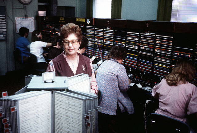 Margaret Flatus, switchboard supervisor, scans the base directory while switchboard operators work in the background. The Switchboard Center is part of the 1974th Communications Group, Air Force Communications Command